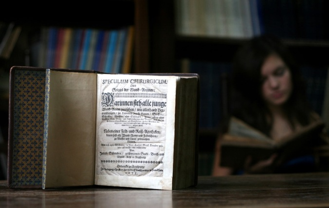 Image: Girl Reading Next to Old Book